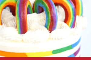 Buttercream Rainbows on rainbow striped cake with text overlay for Pinterest