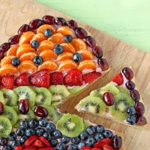 Easter Fruit Pizza on a wooden cutting board with a slice removed