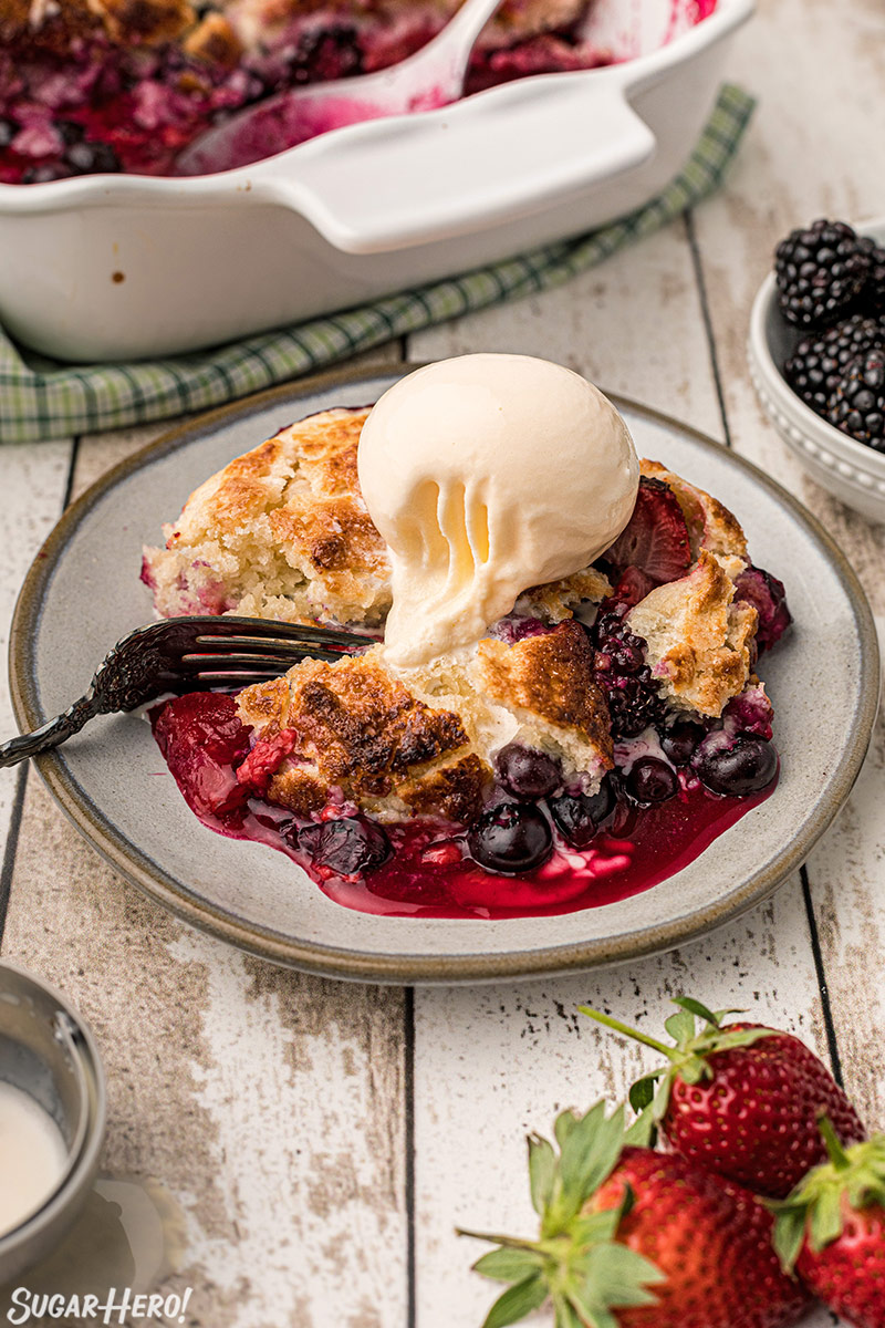 Berry cobbler on a plate with a scoop of ice cream on top