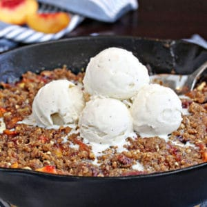 Cast iron skillet filled with peach crisp, with vanilla ice cream scoops on top