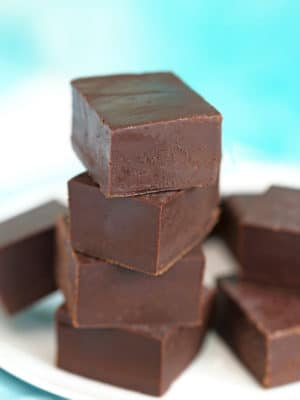 Stack of chocolate fudge pieces on a white plate