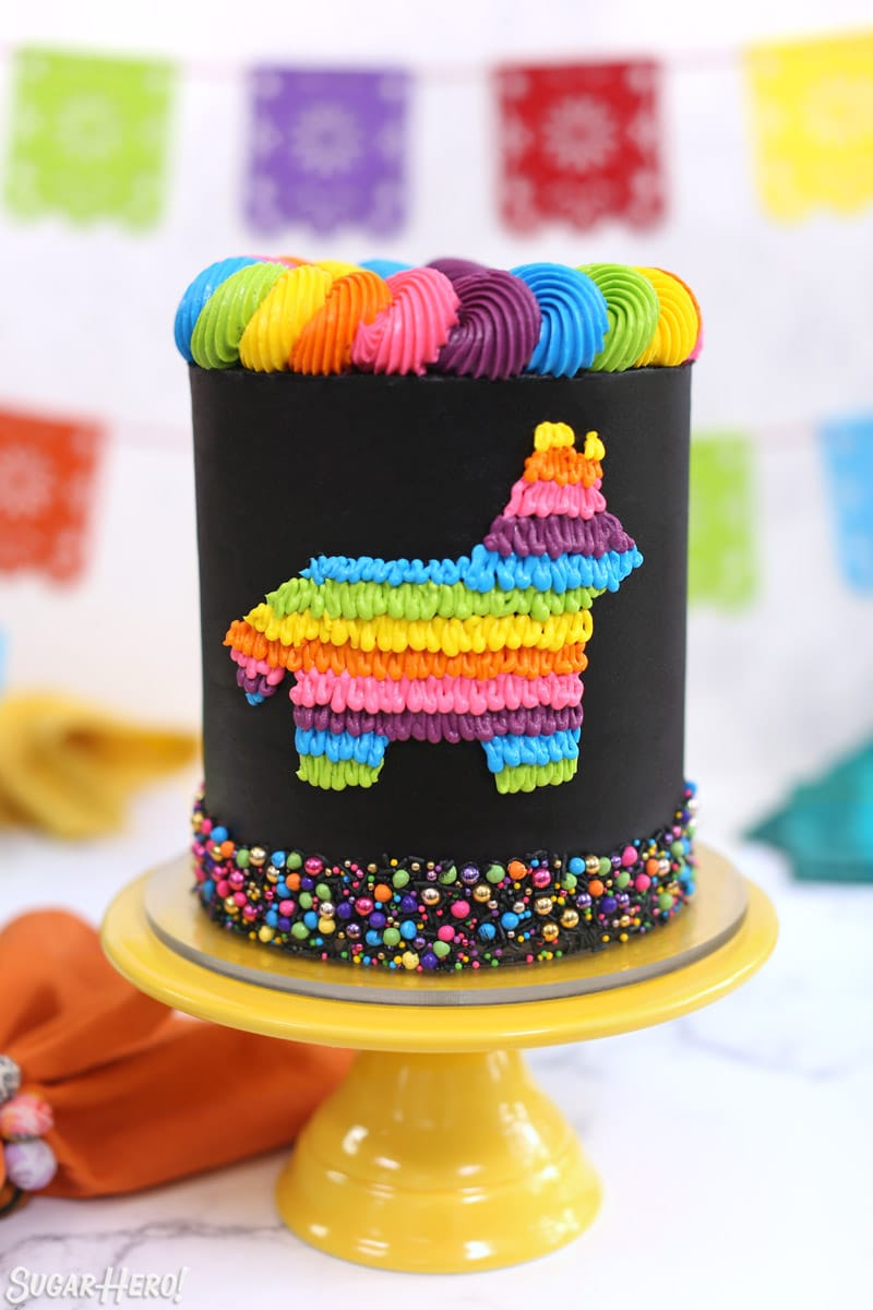 Black pinata cake decorated with neon buttercream design on a yellow cake stand