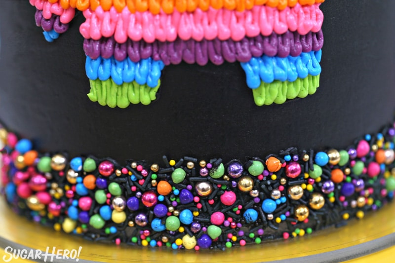 Close-up of colorful sprinkle border on black pinata cake