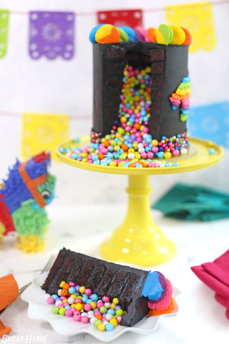 Chocolate pinata cake with candy inside on a yellow cake stand with a single piece in front