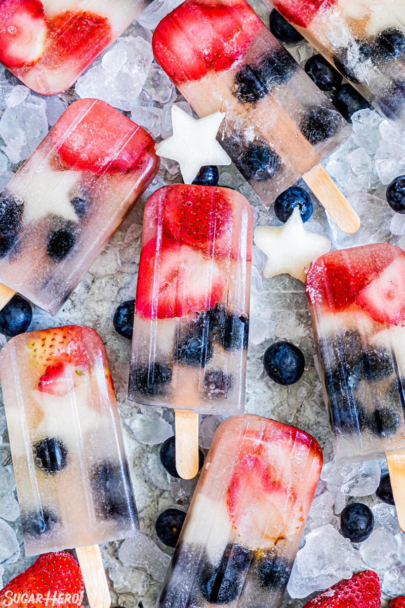 Homemade Fruit Popsicles on a bed of ice with fruit scattered around