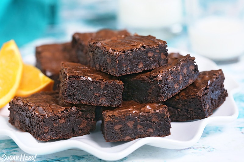 Pile of five chocolate orange brownies on a white plate.