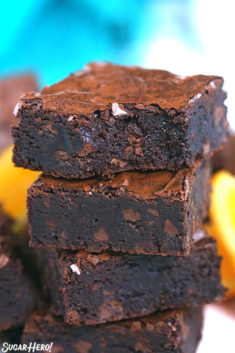 Stack of four chocolate orange brownies with a bite taken out of the top one.