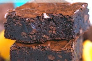 Stack of three chocolate orange brownies with a bite out of the top brownie.