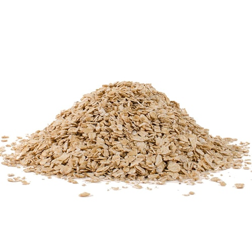 Rolled oats in a pile on a white surface.