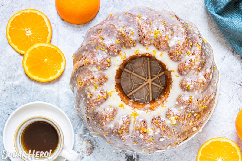 Overhead shot of orange bundt cake with orange glaze, with coffee cup at the side.