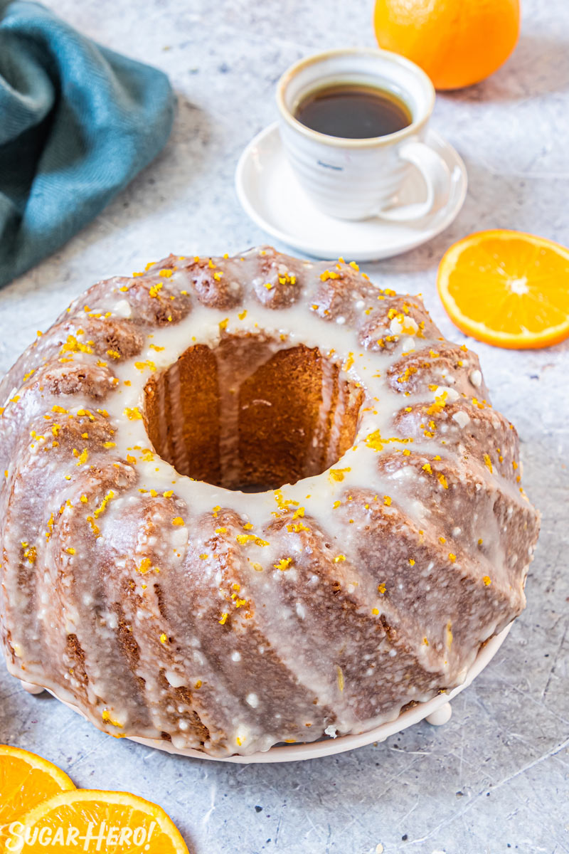 Orange bundt cake with orange glaze, with coffee cup and teal napkin in background.