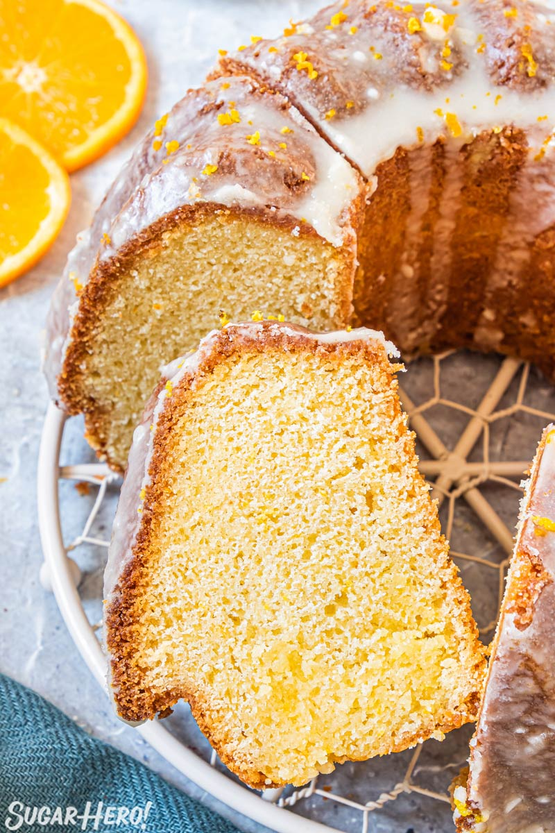 Sliced bundt cake on a wire rack with one piece leaning to the side.