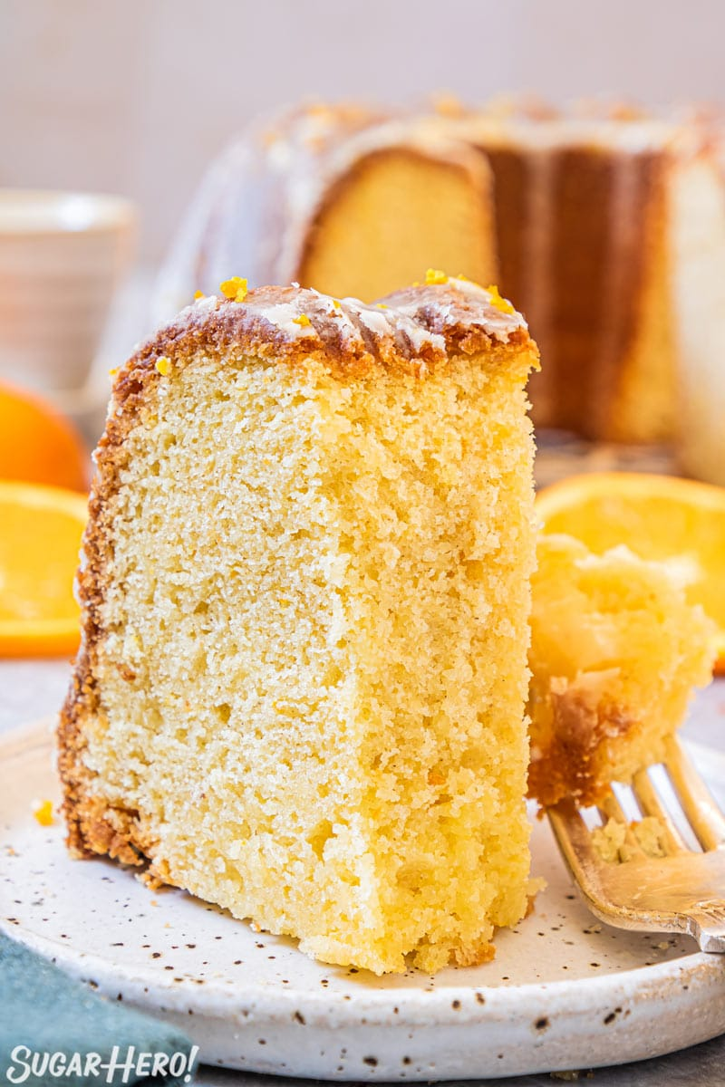 Slice of orange bundt cake on plate with a bite taken out of it.