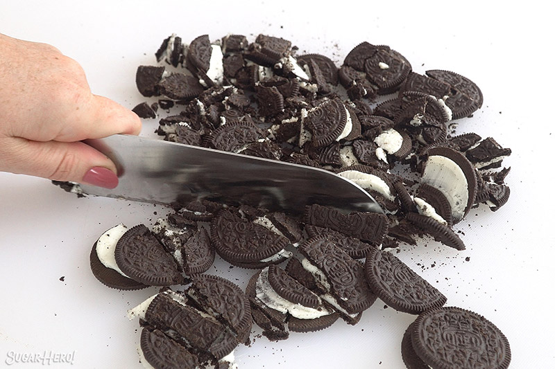 Large knife slicing Oreos on a white cutting board.
