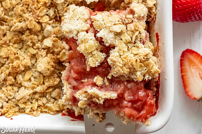 Spatula removing a serving of Strawberry Crisp from the baking pan.