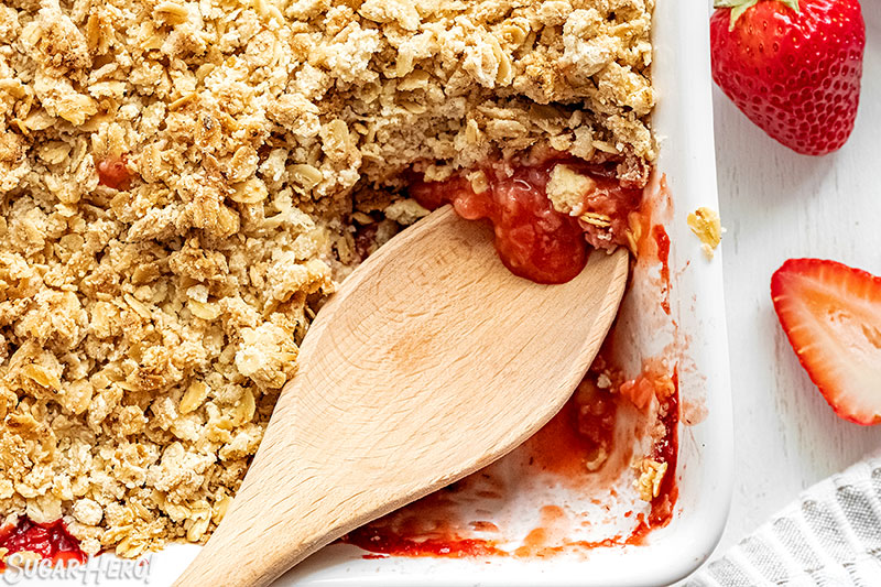 Wooden spoon scooping out Strawberry Crisp from the baking pan.