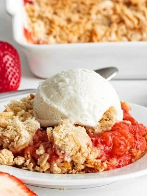 Strawberry Crisp on a white plate with a scoop of vanilla ice cream on top.