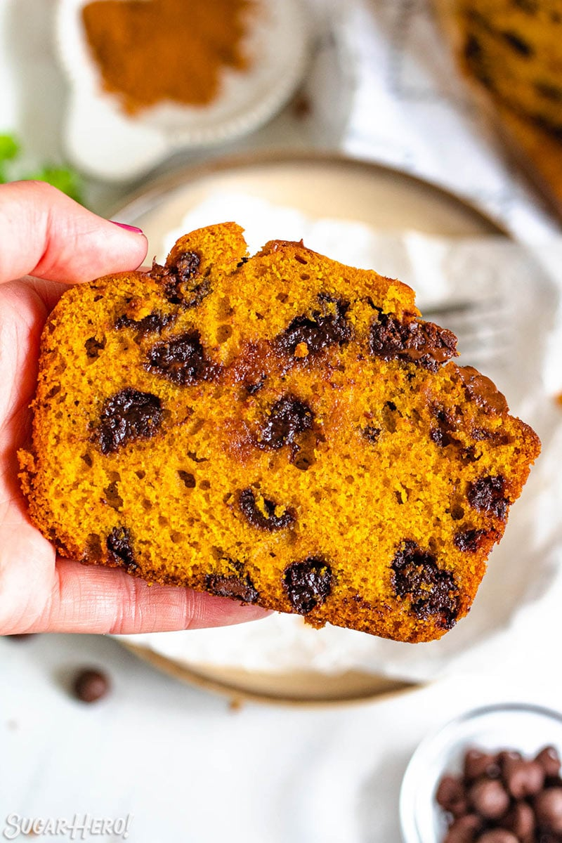 Hand holding a slice of pumpkin bread studded with melted chocolate chips.