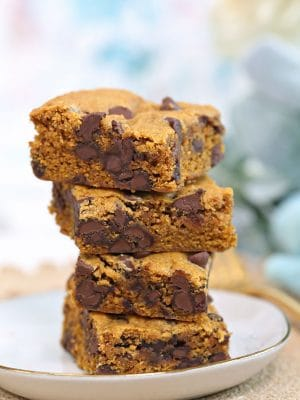 Stack of four Pumpkin Chocolate Chip Bars on a white plate.